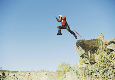 A man jumps into the abyss against the sky.