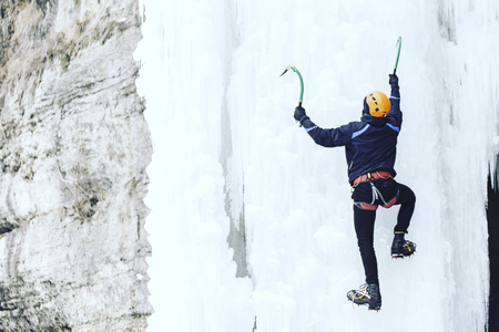 Man climbing a frozen waterfall with ice tool. Stock Photo