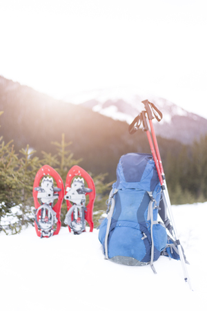 Winter trekking in the mountains. The backpack stands on a slope with a view of the mountains.