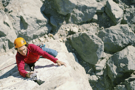A climber man climbs to the top of a cliff.