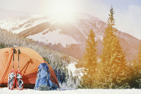 Winter trek in the mountains. The tent stands on the mountainside against the backdrop of the mountains. Stock fotó
