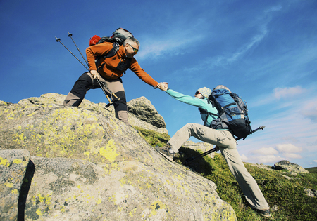 Couple Man and Woman help giving hands climbing rocky mountains Love and Travel Lifestyle concept hiking adventure vacations outdoor Zdjęcie Seryjne - 93206255