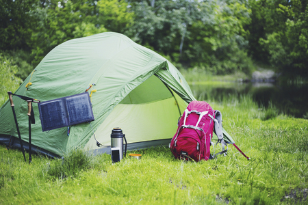 Camping on the river bank. The solar panel hangs on the tent. Imagens - 93206278