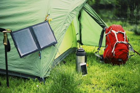 Camping on the river bank. The solar panel hangs on the tent.