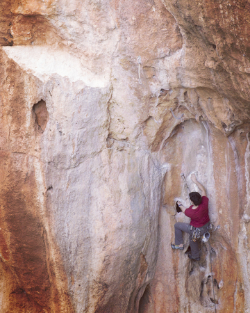 Rock-climbing in Turkey. The climber climbs on the route. Photo from the top. Stock Photo