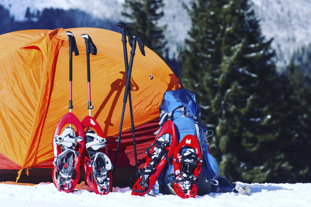 Winter hike in the mountains. Snowshoes are in the snow near the tent.