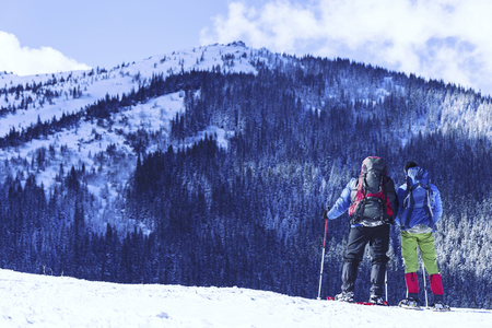 Winter hiking in the mountains on snowshoes with a backpack and tent. Stock fotó