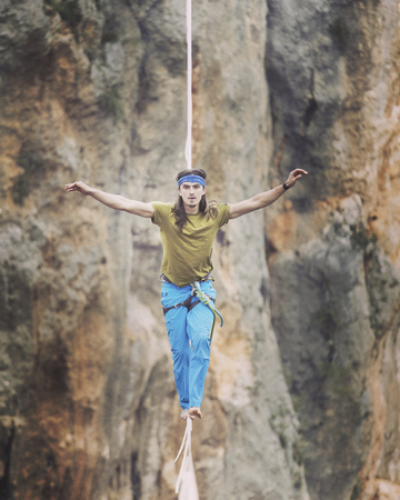 Man balancing on the rope concept of risk taking and challenge.