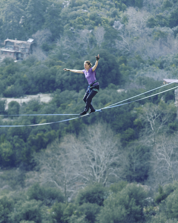 Woman balancing on the rope concept of risk taking and challenge.