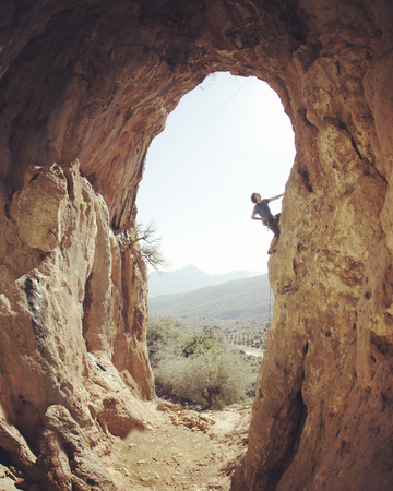 Male rock climber hanging with one hand on challenging route on cliff and putting chalk on another