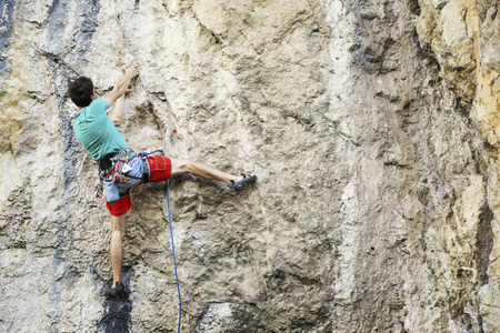 Scalatore di roccia dell'uomo. Lo scalatore si arrampica su una parete rocciosa. L'uomo fa una mossa difficile. Archivio Fotografico