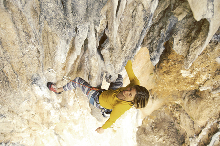 The girl climbs the rock. Fitness in nature and rock climbing. The climber climbs up. Reklamní fotografie