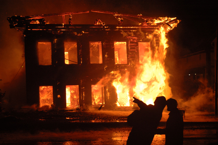 Two firemen at work showing the burning house Stock Photo