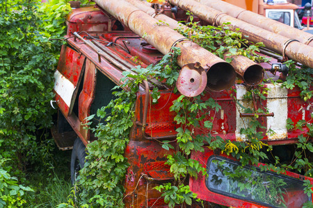 old fire truck in the foliage at the dump Standard-Bild