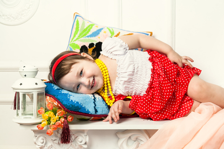 mantelpiece: The child lying on the mantelpiece in white interior