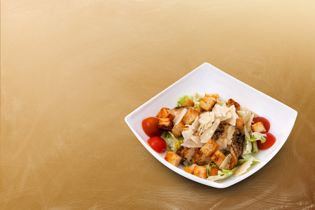 chicken caesar salad: Chicken Caesar Salad with Cheese and Croutons on a beautiful brown background