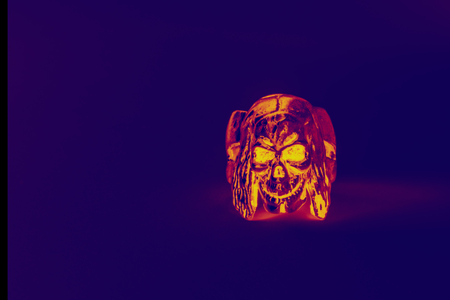 The skull ring glows dangerous and yellow on a purple background. Helowin