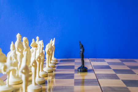 Chess on black background. A black pawn is facing an enemy army