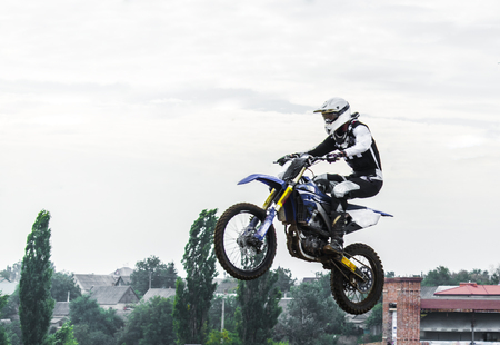 motorcross: The racer on a motorcycle participates in a motocross race, jumps on a springboard. The black suit of the chaser is white. Stock Photo