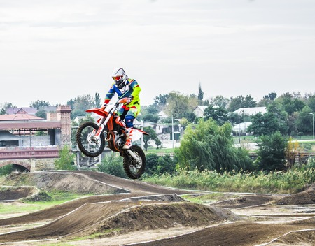 The racer on a motorcycle participates in a motocross race, jumps on a springboard. He took off high on a motorcycle. Dangerous sport