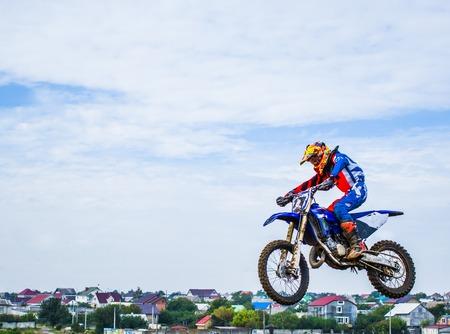 Deporte extremo motocross El atleta se quita una motocicleta en un trampolín. Concurso en el mestnosti de la ciudad. Saltos de salto muy alto Foto de archivo