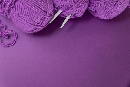 Background with knitting tools and accesories, colorful purple skein yarn, hobby concept, copyspace