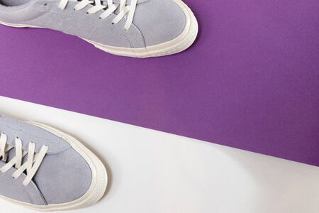White and grey mens sneakers on a white and purple background. Flat spoon, top view minimal background. The concept of a Fashion blog or magazine.