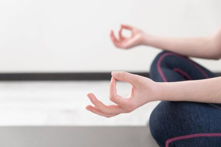 Young sporty woman practicing yoga lesson sitting in Sukhasana exercise