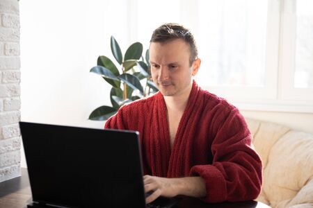 A young man smiles as he reads on a laptop screen while relaxing on a comfortable sofa at home in dressing gowns