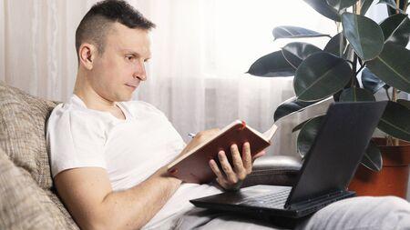 A focused European male freelancer takes notes studies working with a laptop, a young professional writes an essay in a notebook prepares for a test exam and sits at home on the couch. Remote work