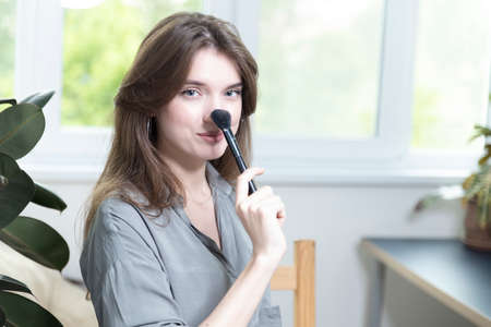 A beautiful girl is sitting in a bright room and making a selfie video for a fashion blog. The woman keeps a blog online and makes a photo. Fashion cosmetics reviewer