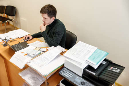 A casual businessman works in an office, sits at a Desk, types on a keyboard, looks at a computer screen. Concept of office work. 写真素材
