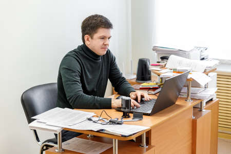 A casual businessman works in an office, sits at a Desk, types on a keyboard, looks at a computer screen. Concept of office work. Banco de Imagens