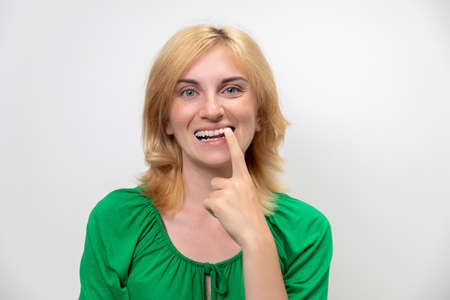 Portrait of a beautiful woman with braces on her teeth, isolated on a white background. The concept of the perfect smile