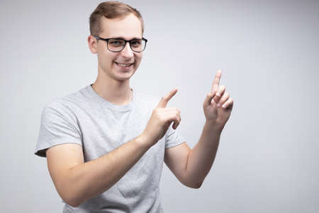 A happy male actively gestures, expresses positive emotions after receiving a salary or bonus, and enjoys his success isolated above a white concrete wall. The concept of people, happiness, and body language
