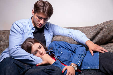 Romantic couple, handsome boyfriend hugging sad unhealthy female girlfriend feeling support and empathy on couch