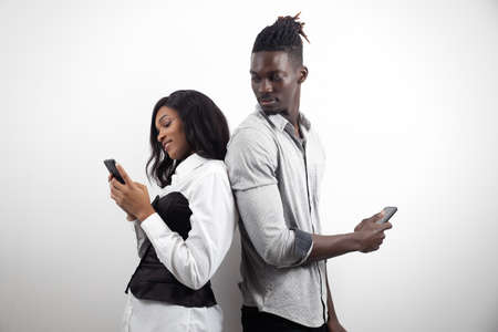 Happy young african american couple using modern phones, social media apps, shopping online on white studio background