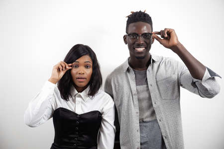 Positive african-american couple managers showing little size of prices with fingers on white studio background