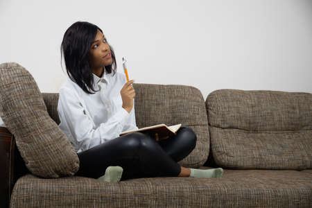 Thoughtful dreamy young african american female sitting on couch making notes, planning week to-do list write in notepad