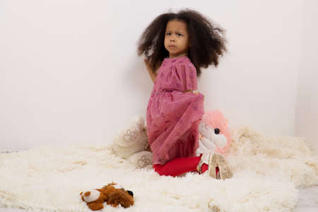 Portrait images of a 3-year-old African girl standing on a light blanket on the floor with a face depicting anger and resentment, a concept for Children with emotional expressions.