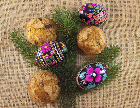 easter eggs with muffins and tree branch on sacking