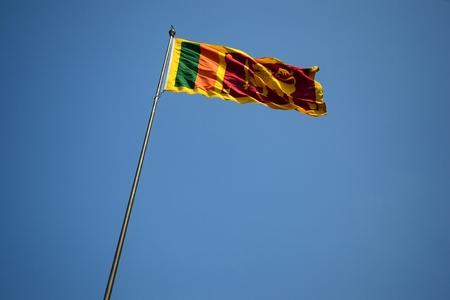 Sri Lanka flag waving on a pole against clear blue sky. Фото со стока