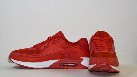 Red sneakers with a white sole on a white background, close-up, right sneakers are directed towards the camera, and left-handed towards 90 degrees