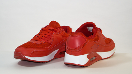 Red sneakers with a white sole on a white background, close-up, right sneakers are directed away from the camera, and the left ones are directed towards the camera Фото со стока