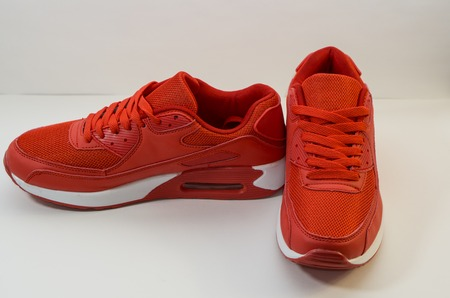 Red sneakers with a white sole on a white background, close-up, the right sneakersis directed towards the camera and the left is pointing to the side, view at an angle of 90 degrees