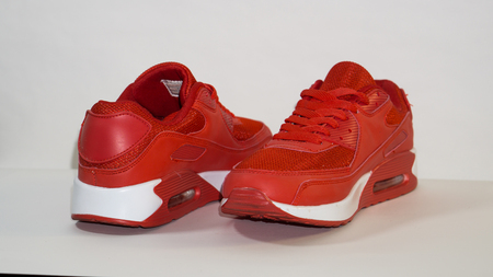 Red sneakers with a white sole on a white background, close-up,left sneakers are directed away from the camera, and the right ones are directed towards the camera