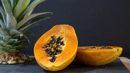 The papaya is cut into two halves, the stand is a stone board with a wooden frame, near the Papay there is a cut off top of the pineapple, the background is black Stok Fotoğraf
