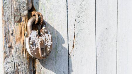 Antique padlock on a wooden door. Metal vintage lock. Rusty old door lock.
