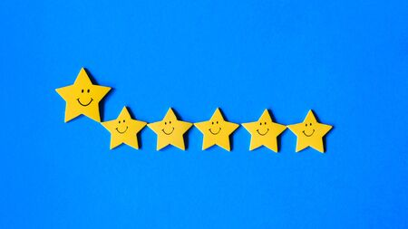 leadership and teamwork concept, big yellow star leads small stars on a blue background