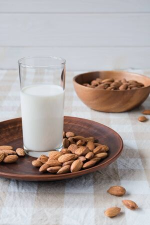 healthy food concept, almonds and glass of milk on a plate on the table